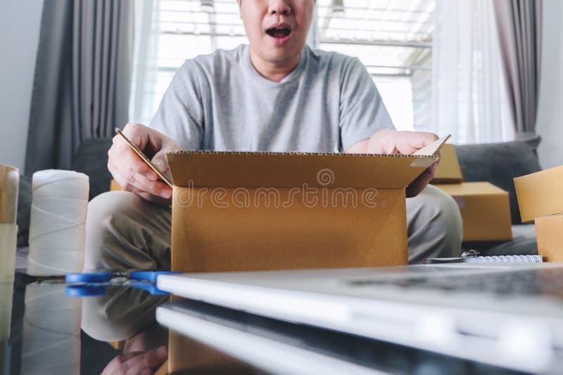 Colis de petite entreprise pour embarquer, bo?te en ligne de paquet d'achats d'ouverture heureuse d'homme avec le colis tout en s photographie stock libre de droits
