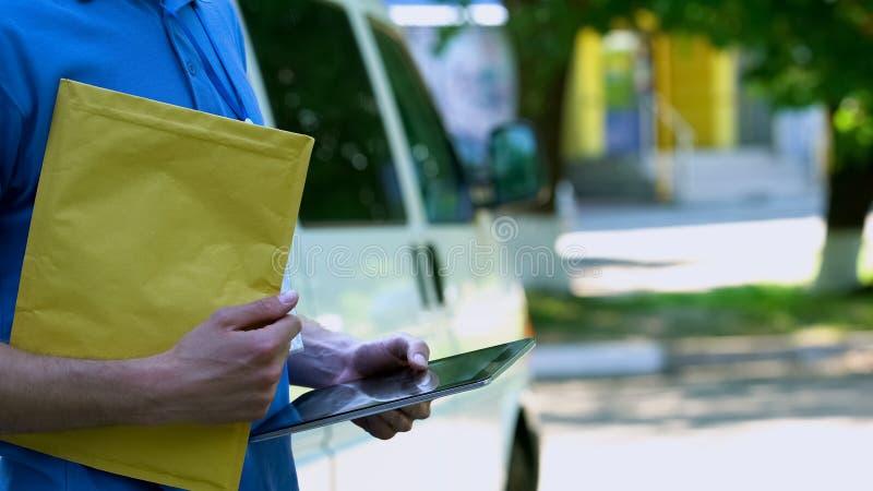 Colis et comprimé de participation de garçon de livraison avec la demande de clients, service photographie stock