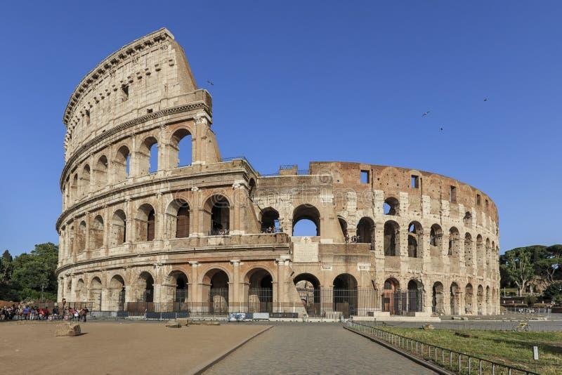 Coliseu em um dia ensolarado em Roma, Itália, com um grupo pequeno de turistas foto de stock