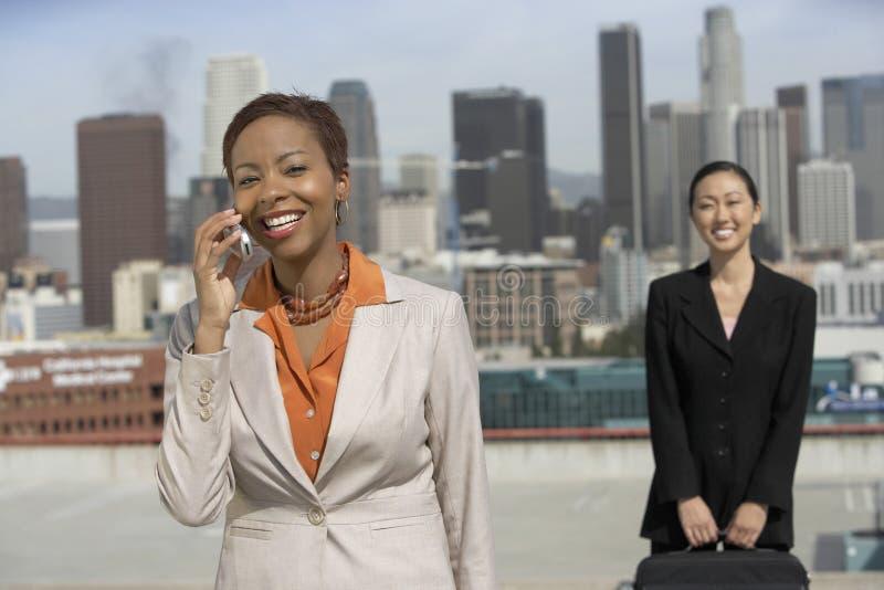 Collègue d'On Call With de femme d'affaires tenant la serviette contre le paysage urbain image libre de droits