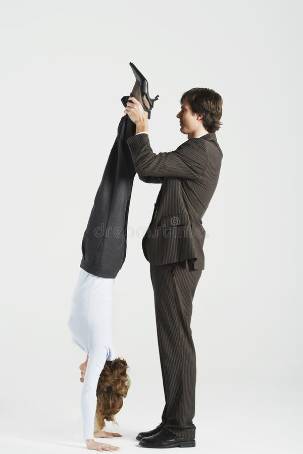 Collègue féminin de Holding Legs Of d'homme d'affaires se tenant sur des mains image libre de droits