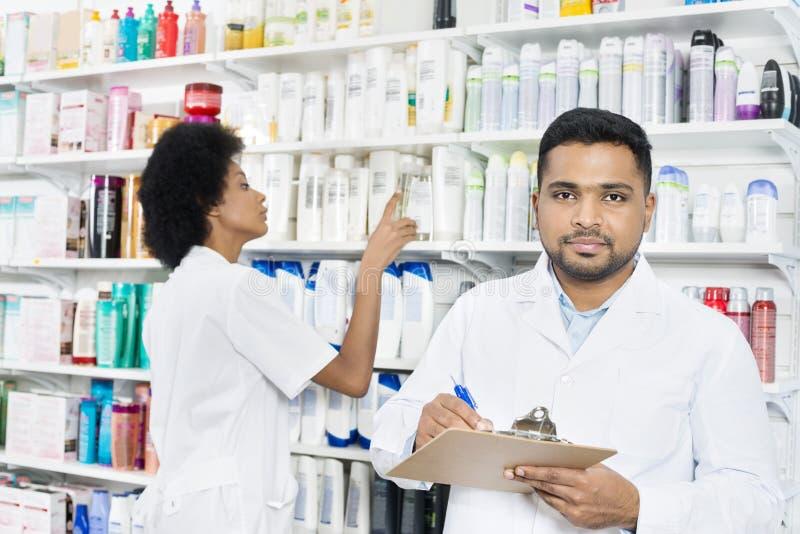 Collègue masculin de Holding Clipboard While de pharmacien s'chargeant du Stoc photos stock