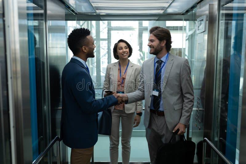 Collègue multi-ethnique d'usiness agissant l'un sur l'autre les uns avec les autres dans l'ascenseur images stock