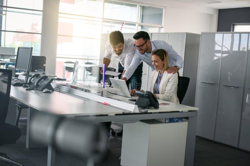 Collègue trois dans le bureau utilisant des gens d'affaires d'ordinateur dans l'offi image libre de droits