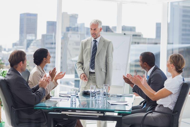 Collègues applaudissant le patron au cours d'une réunion photo libre de droits