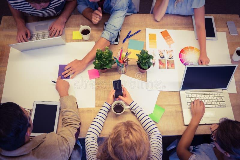 Collègues créatifs avec l'ordinateur portable et le comprimé numérique images stock