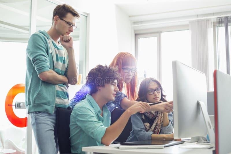 Collègues créatifs d'affaires discutant au-dessus de l'ordinateur dans le bureau image stock