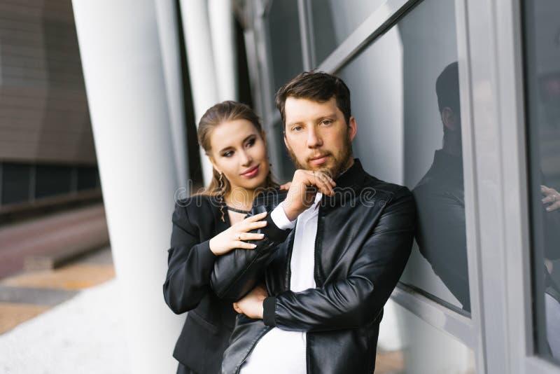 Collègues d'affaires élégants en habit noir et blanc Le type regarde la caméra et tient la main près de son menton images stock