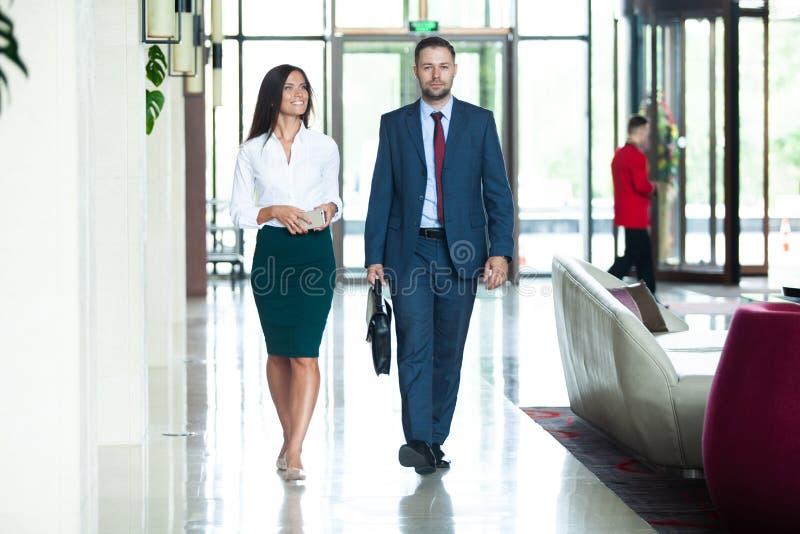 Collègues d'affaires agissant l'un sur l'autre les uns avec les autres tout en marchant dans le couloir au bureau photo stock