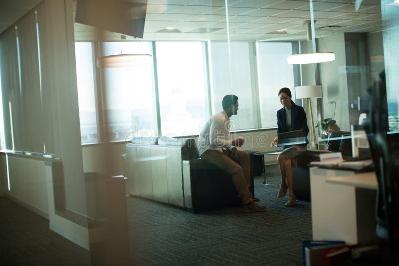 Collègues d'affaires agissant l'un sur l'autre tout en se reposant sur le sofa dans le bureau image stock