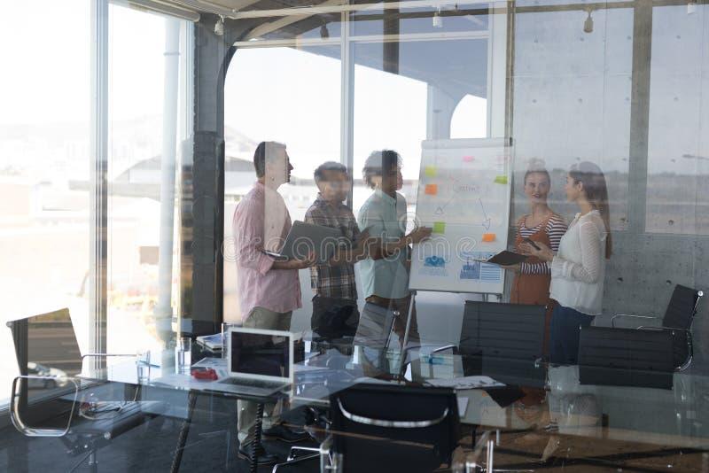 Collègues d'affaires discutant au-dessus du tableau de conférence dans le bureau image libre de droits