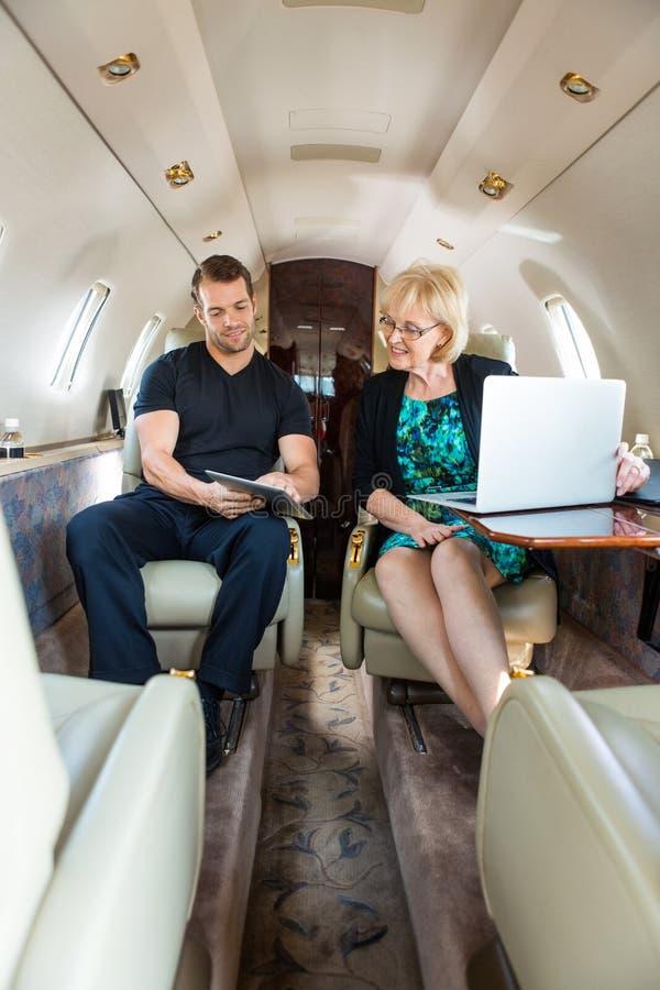 Collègues d'affaires discutant sur le jet privé image stock