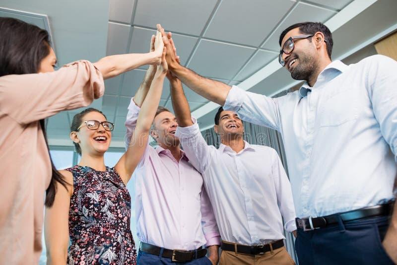 Collègues d'affaires donnant la haute cinq au cours de la réunion dans le bureau photos stock