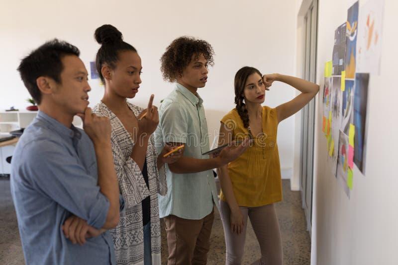 Collègues d'affaires regardant des graphiques et des notes collantes dans le bureau photos stock