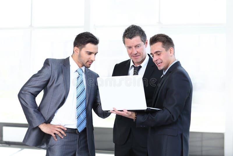 Collègues d'affaires regardant un ordinateur portable, se tenant dans le lobby du bureau image stock