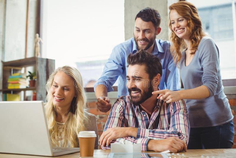 Collègues d'affaires souriant tout en regardant l'ordinateur portable image stock