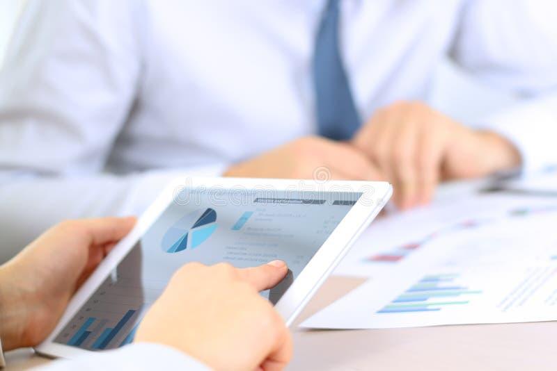 Collègues d'affaires travaillant et analysant les graphiques financiers sur un comprimé numérique photographie stock