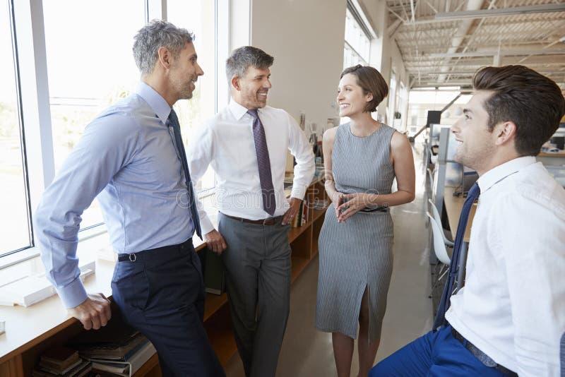 Collègues d'entreprise constituée en société parlant dans un bureau ouvert de plan images libres de droits