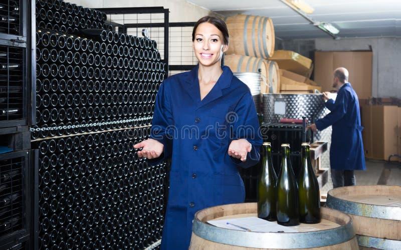 Collègues d'homme et de femmes regardant le vin pétillant dans le remplaçant de bouteille image stock