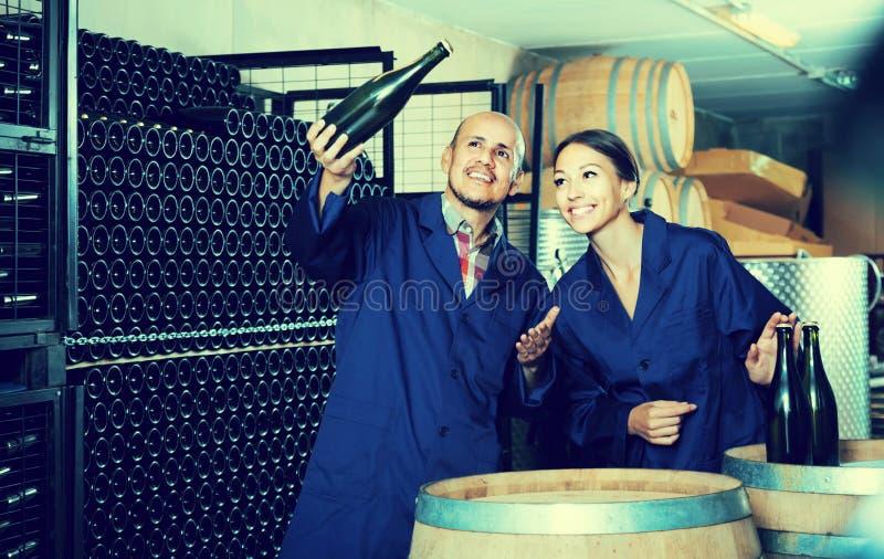 Collègues d'homme et de femmes regardant le vin pétillant dans le remplaçant de bouteille photos libres de droits