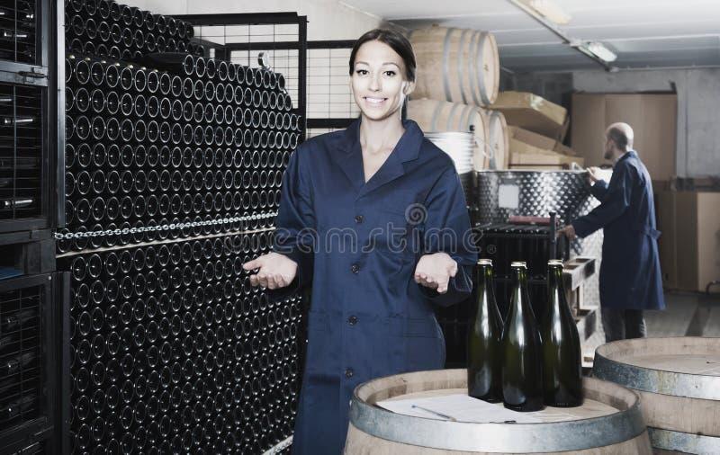 Collègues d'homme et de femmes regardant le vin pétillant dans le remplaçant de bouteille photo libre de droits