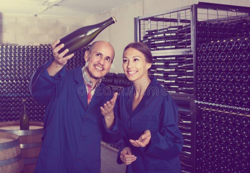 Collègues d'homme et de femmes regardant le vin pétillant dans le remplaçant de bouteille photographie stock libre de droits
