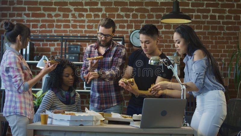 Collègues dans le bureau mangeant de la pizza ensemble photo stock