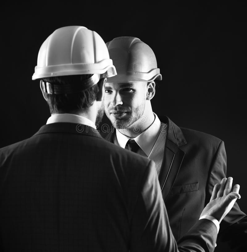 Collègues dans les costumes et les casques formels de bâtiment Concept d'entreprise de construction photos stock