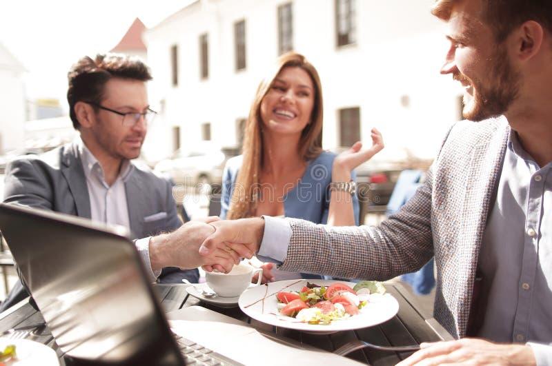 Collègues de poignée de main à une table dans un café de rue image libre de droits