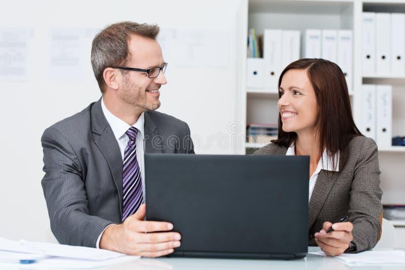 Collègues de sourire d'affaires dans le bureau photo stock