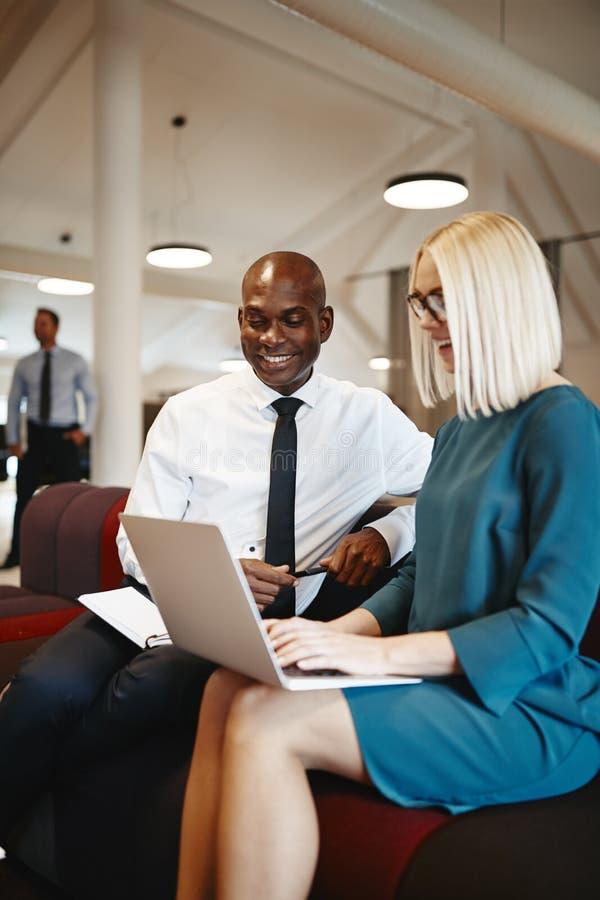Collègues de sourire d'affaires discutant le travail ensemble sur un bureau image stock