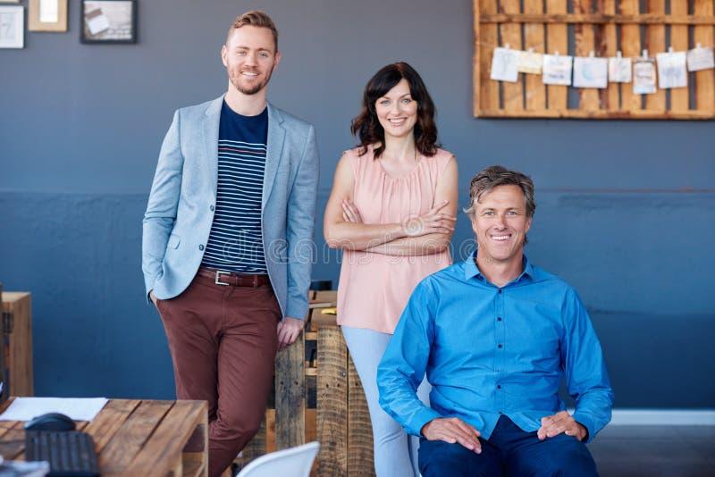 Collègues de sourire de travail travaillant ensemble dans un bureau moderne image stock