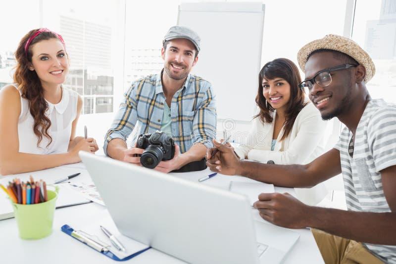 Collègues de sourire travaillant avec l'appareil photo numérique photo stock