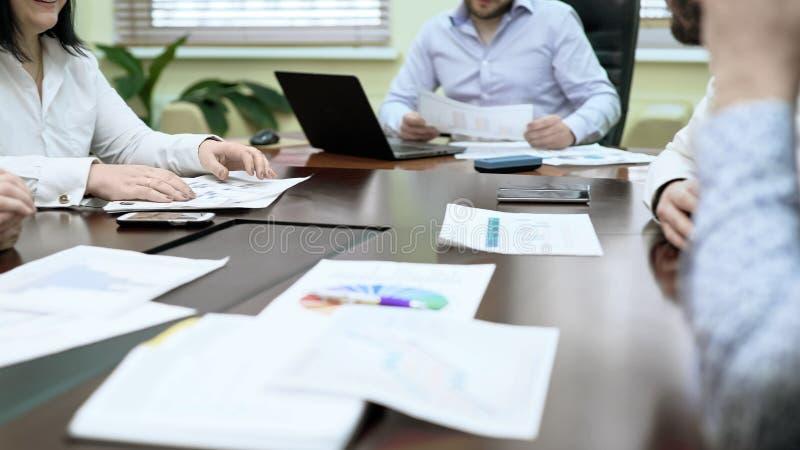 Collègues discutant des données lors de la réunion d'affaires, partageant des diagrammes de statistique, équipe photographie stock