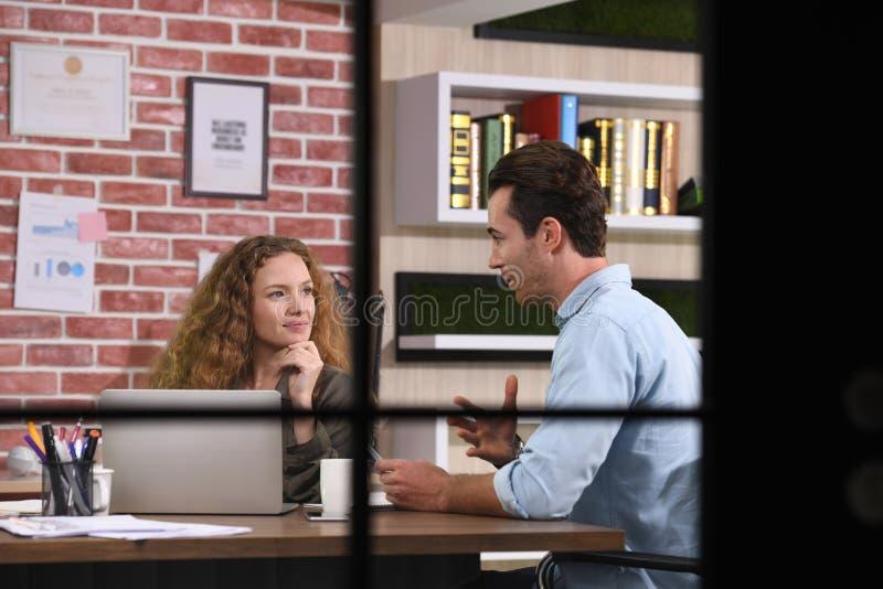 Collègues discutant le travail utilisant un ordinateur portable dans le bureau photographie stock libre de droits