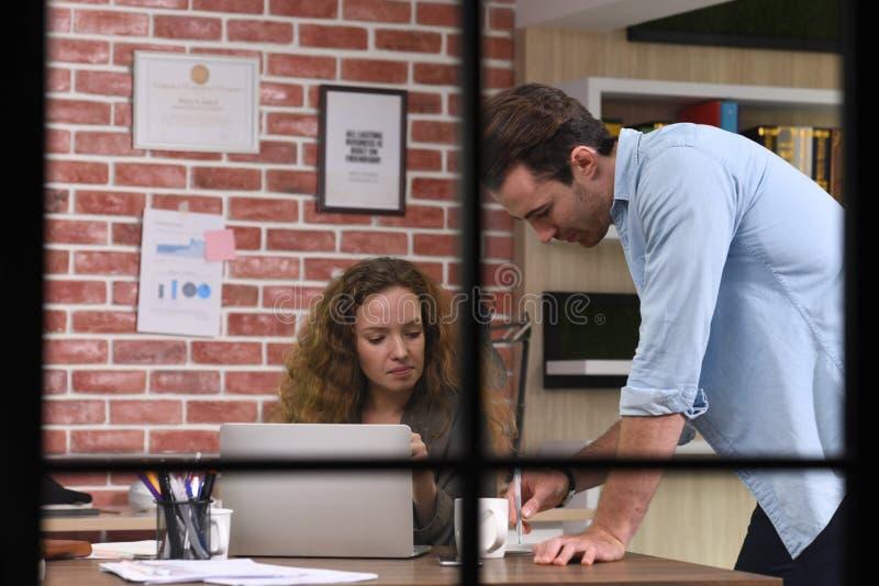 Collègues discutant le travail utilisant un ordinateur portable dans le bureau photos stock