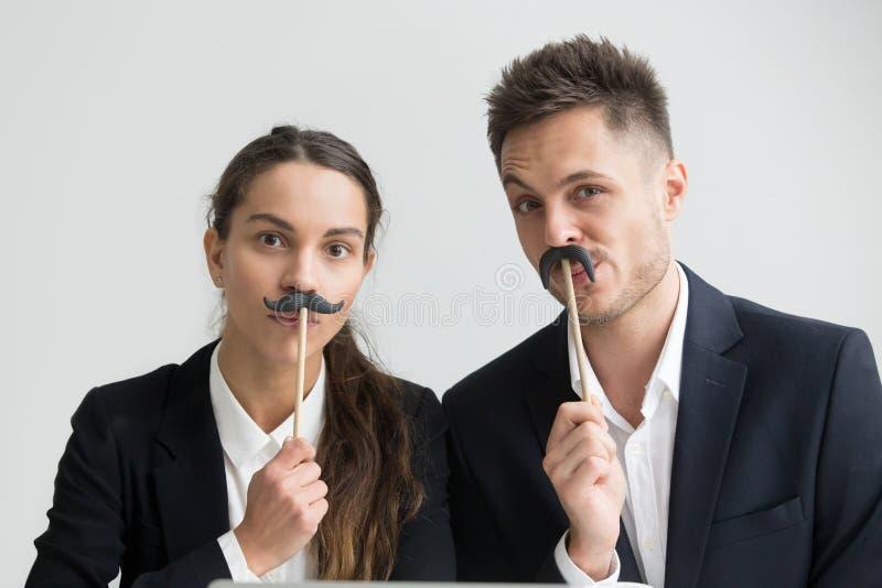 Collègues drôles faisant les visages idiots tenant la fausse moustache, têtes images libres de droits