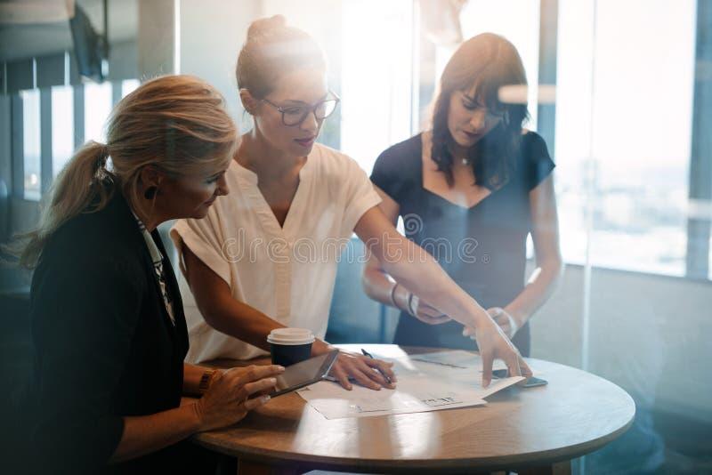Collègues féminins ayant une réunion debout autour de la table images libres de droits