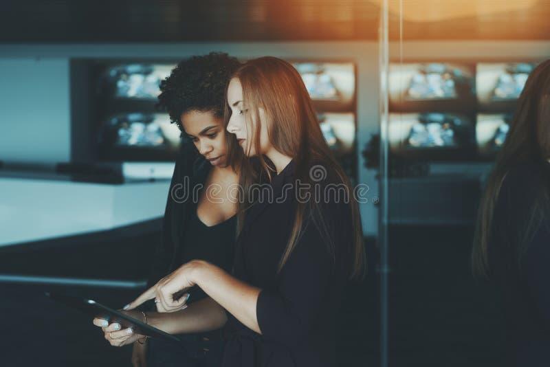 Collègues féminins de différentes courses utilisant le comprimé numérique dedans  photo stock