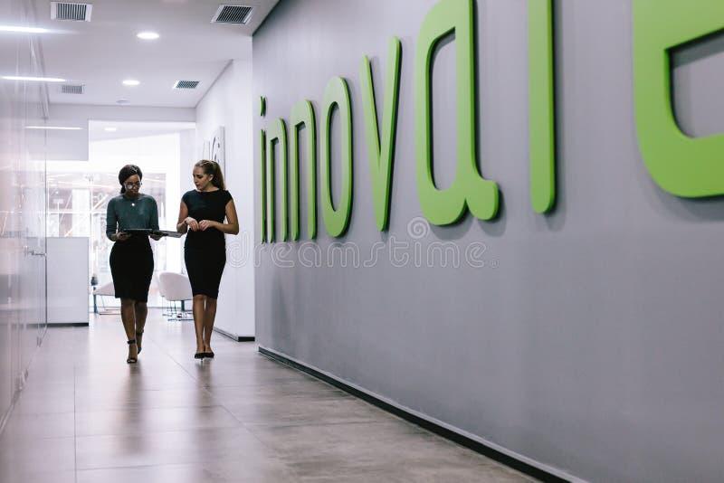 Collègues féminins marchant dans le couloir de bureau images stock