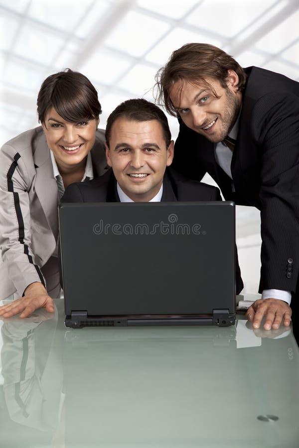 Collègues heureux derrière un ordinateur portatif images libres de droits