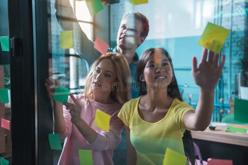 Collègues heureux marquant des notes de post-it sur la fenêtre images stock
