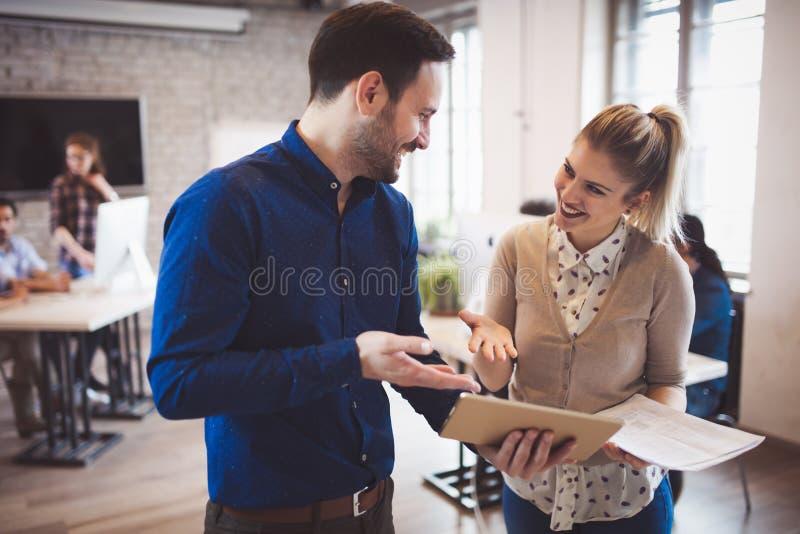 Collègues heureux réussis communiquant dans le bureau de société photographie stock