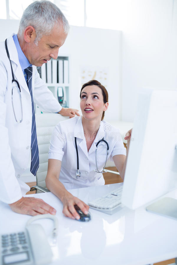 Download Collègues Médicaux Concentrés Discutant Et Travaillant Avec L'ordinateur Image stock - Image du infirmière, concentré: 56482919