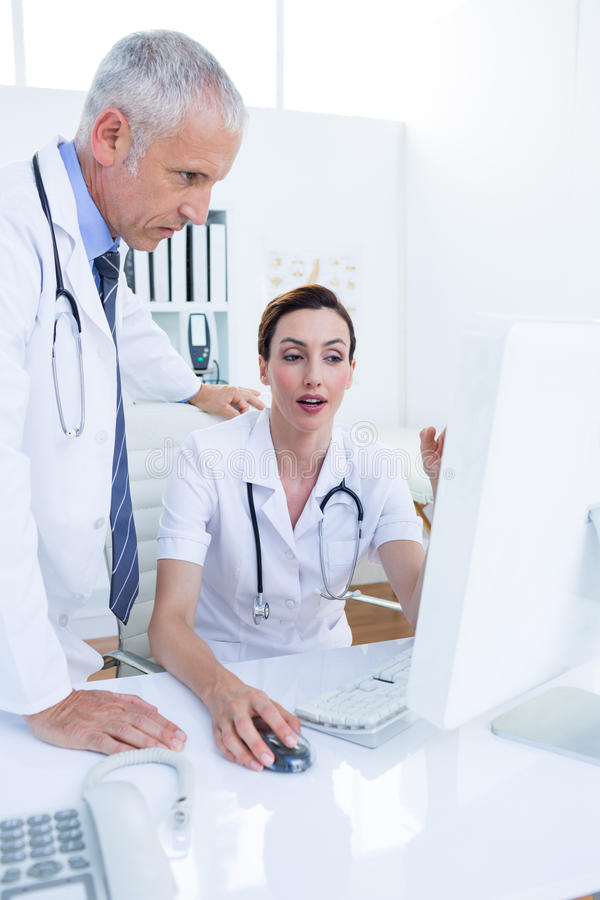Download Collègues Médicaux Concentrés Discutant Et Travaillant Avec L'ordinateur Image stock - Image du médical, hôpital: 56484651