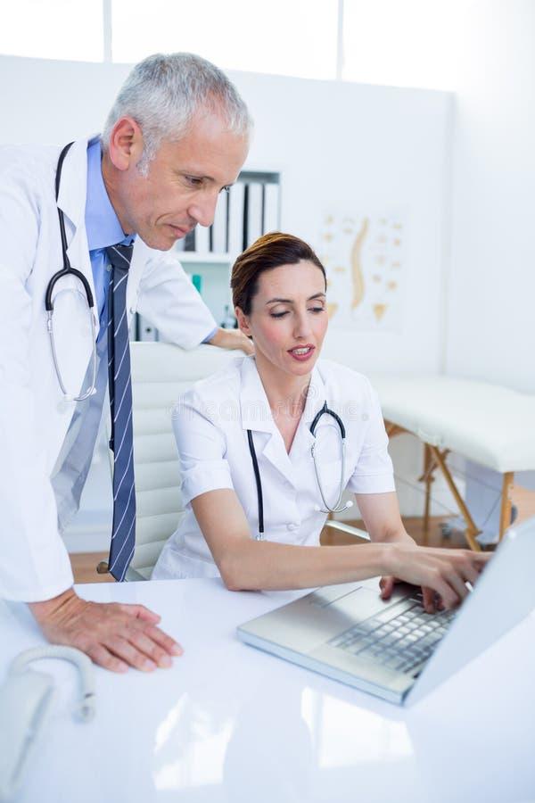 Download Collègues Médicaux Concentrés Discutant Et Travaillant Avec L'ordinateur Portable Image stock - Image du métier, médical: 56483973