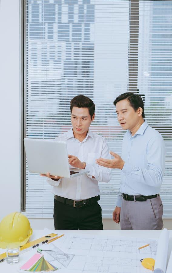 Collègues masculins discutant des idées au sujet du projet dans le bureau, archit image stock