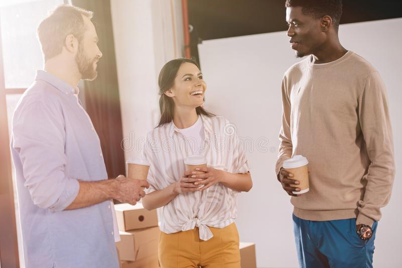 collègues multi-ethniques heureux tenant les tasses de papier et parlant dans le nouveau bureau photo stock