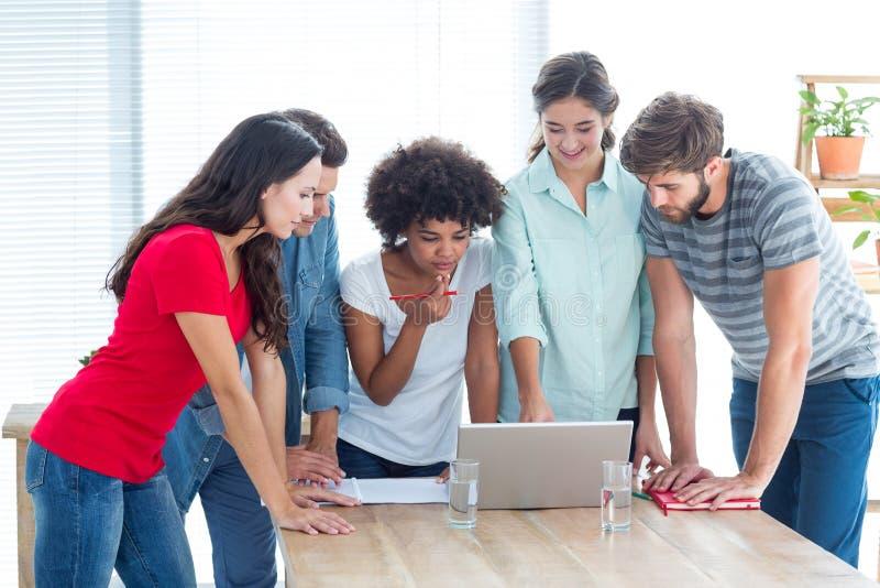 Collègues recueillis autour d'un ordinateur portable au bureau photo libre de droits