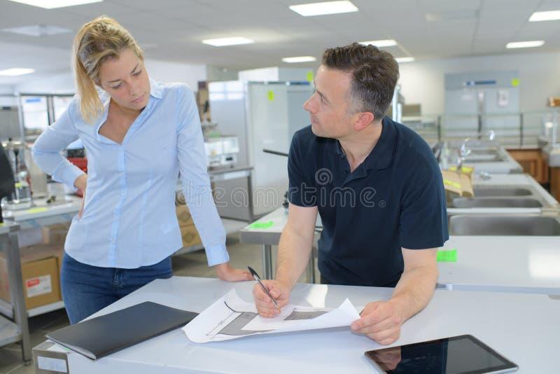 Collègues sûrs discutant des plans dans le bureau images libres de droits